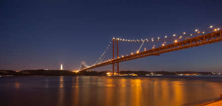25th: The 25th April bridge in Lisbon at night under a full moon. The bridge is a cable- stayed bridge at 2.27km and is very similar to the Golden Gate bridge in San Francisco Stock Photo
