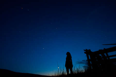 stargazing: Silhouette of a woman against the night sky stargazing.