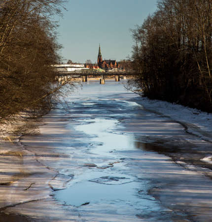 winter thaw: Thawing River with Distant Church Stock Photo