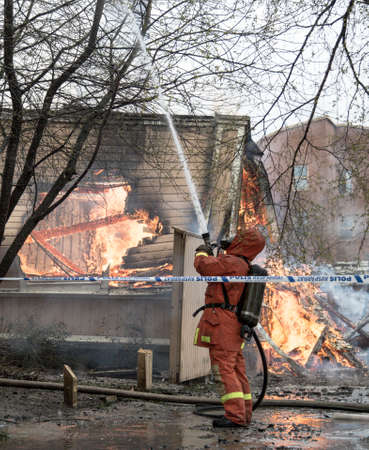 residential tree service: Firefighter Fighting Fire in residential house in Sweden.