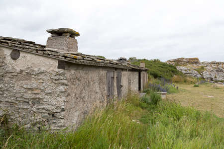 fishing hut: Old Fishing Hut in Gotland, Sweden with sea stacks next to it. Stock Photo