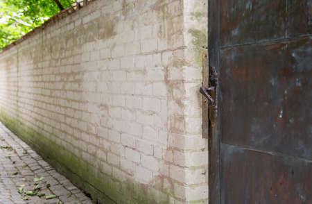 cobblestone: Metal Door in Brick Wall with cobblestone street.