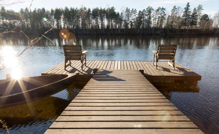 two chairs: Two Chairs on Pier in River Stock Photo
