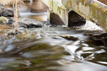 underneath: Water Pouring Underneath Logs Stock Photo