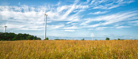 kinetic energy: Wind Power Stations in Field with a partly cloudy sky.