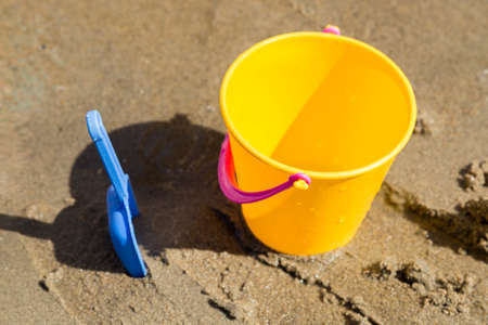 bucket and spade: Toy Spade and Bucket in Sand. Stock Photo