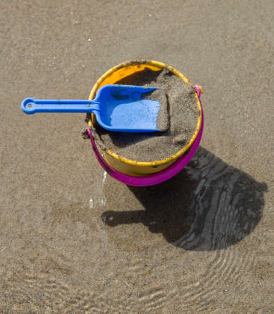 bucket and spade: Toy Spade and Bucket on a Beach with sand.