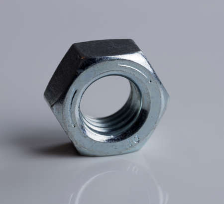 metal fastener: Hardware Nut Close Up on gray background. Stock Photo