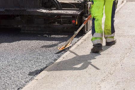 paver: Asphalt Worker Laying Down Asphalt with the paver behind.