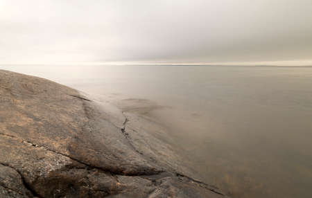 shorelines: Rocky Shore by Ocean with a cloudy sky.