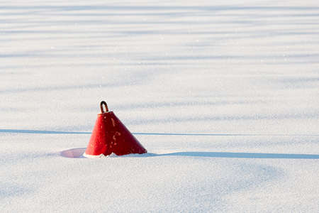 buoy: Red Buoy in frozen Water with snow. Stock Photo