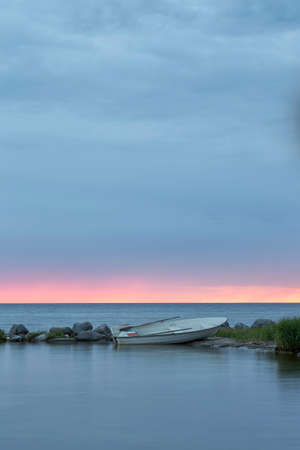 Roeiboot door oceaan bij zonsondergang met een gedeeltelijk bewolkte hemel.