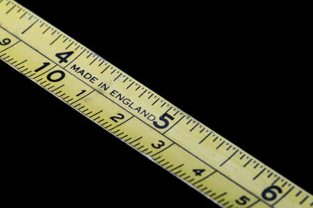 Yellow tape measure Close Up on black background. Reklamní fotografie