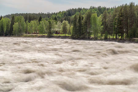 The Rapids at Renforsen in Vindeln, Sweden with a partly cloudy sky and red houses. Stock fotó