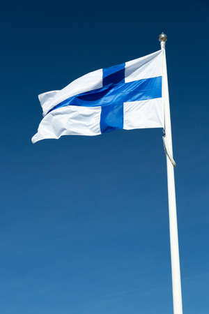 The Finnish Flag on a Flagpole waving in the wind with a blue sky. Фото со стока