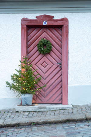 Red Wooden Door with Christmas Decoration. Stock Photo