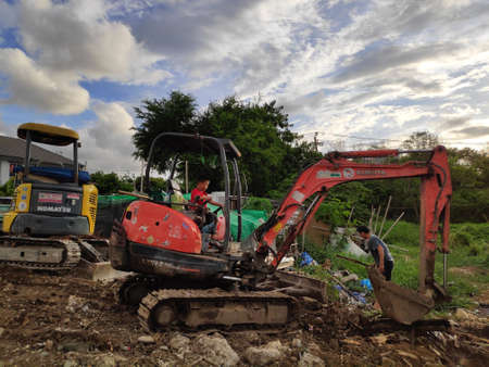 A little boy drives a small excavator to help his father work.