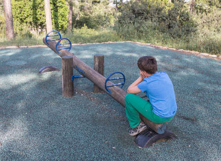 A boy sits by himself on a seesaw in a playground