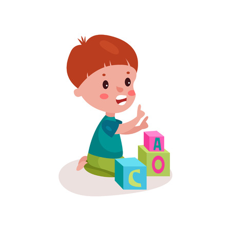 baby toy: Cute redhead little boy sitting on the floor playing with block toy.