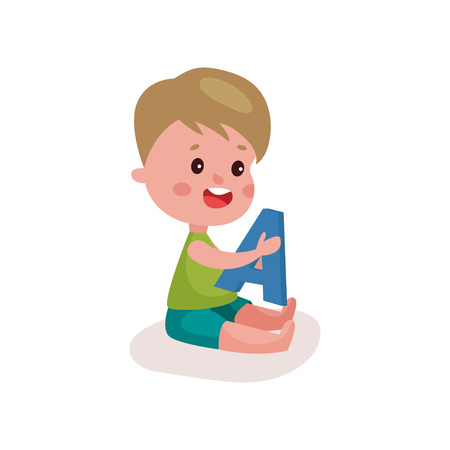 baby toy: Cute little boy sitting on the floor playing with letter A.