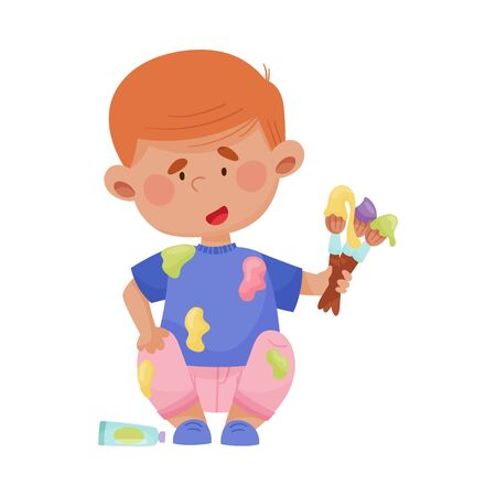 Playful Boy in Stained Clothes Sitting and Holding Paintbrushes and Paints Vector Illustration Vektoros illusztráció