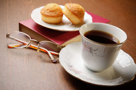 tea and biscuits: Tea, biscuits, book and glasses on wooden background Stock Photo