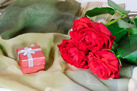 roses rouges: Bo�te-cadeau rouge et trois roses rouges sur un foulard de soie verte