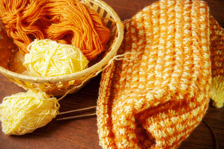 basket embroidery: Woolen yarn and knitting on wooden background.