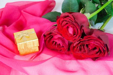 rosas rojas: Caja de regalo de oro y tres rosas rojas en un pa�uelo de seda de color rosa Foto de archivo
