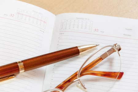 writ: Daily planner with glasses and pen on the table. Selective focus on pen