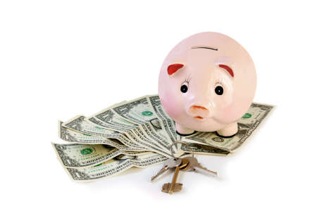 credit crunch: Piggy bank with house keys  and money isolated on white