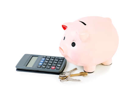 credit crunch: Piggy bank with house keys  and calculator isolated on white