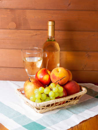 basket: Fruits, wineglass and bottle with wine on a table Stock Photo