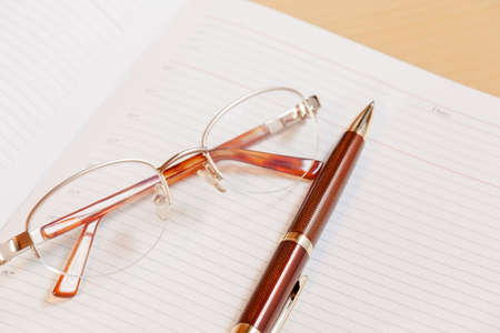 papel de notas: Daily planner with glasses and pen on the table. Selective focus