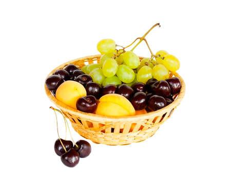 canasta de frutas: frutas de verano brillantes en la canasta aislados en blanco