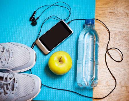 Sport equipment. Sneakers, water, apple, smartphone and earphones on yoga mat