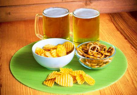 potatoe: Beer mugs, potatoe chips and pretzels on wooden table