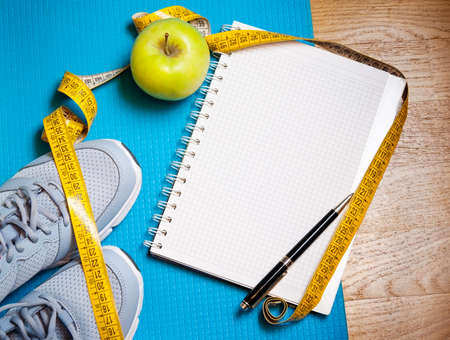 centimeter: Sneakers, centimeter, green apple, notebook. Weight loss,  healthy lifestyle concept