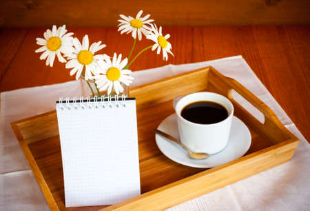 chamomiles: Coffee and chamomiles on wooden table. Selective focus on chamomiles Stock Photo