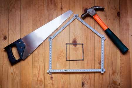 Set of different work tools are in  form of  house: hammer, hand saw, meter, nails over  wooden background. House concept. Build a house. Repairs. Фото со стока