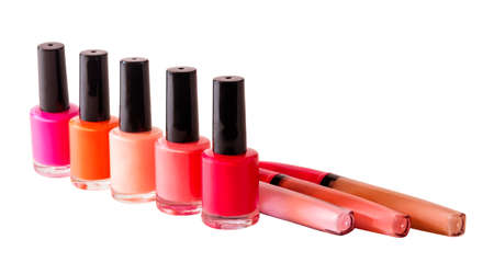 Group of nail polishes and lip glosses isolated on white background. Selective focus
