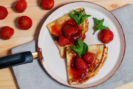 Crepes with fresh strawberries and jam in frying pan