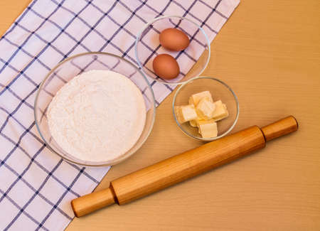 Flour, eggs, butter and rolling pin on table