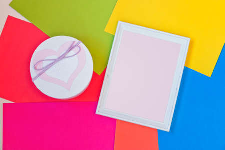 Gift box  and empty white wooden frame on colorful background