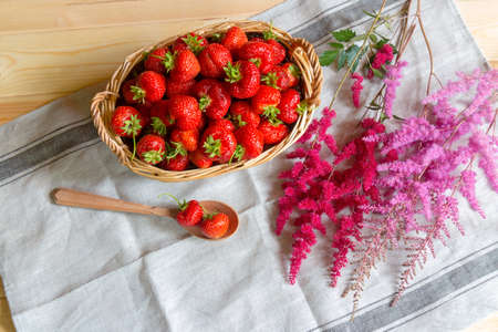 Ripe red strawberries in basket and astilbe flowers on  table. Top view. Фото со стока
