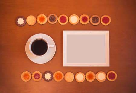 White frame, cup of coffee and assortment of mixed biscuits on rustic wooden background. Top view, copy space.