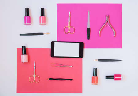 Manicure or pedicure equipment, nail polishes and smartphone on colorful background