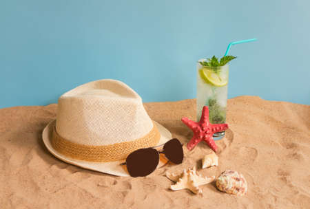 Glass of mojito cocktail, hat, sunglasses, starfishes and seashells on sand beach on blue backdrop. Summer beach holiday concept. View with copy space.