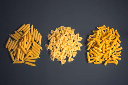Different kinds of raw pasta on dark background. Top view, copy space. 스톡 콘텐츠