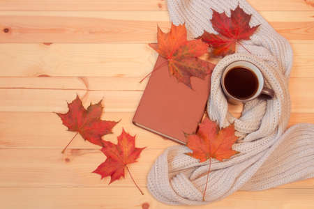 Mug of hot coffee, autumn leaves, book and scarf on wooden background. Top view, copy space.